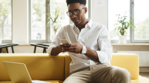 homem sentado utilizando seu smartphone