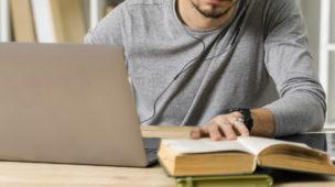 homem lendo um livro em sua mesa de estudos