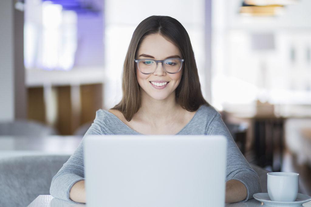 mulher sorridente olhando para seu notebook
