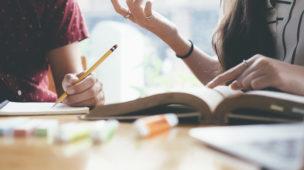 duas pessoas em uma mesa de estudos