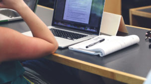 pessoa sentada com notebook e caderno sobre a mesa