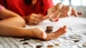 várias moedas empilhadas na mão de uma pessoa