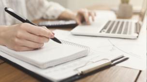 pessoa escrevendo em um caderno e utilizando um notebook