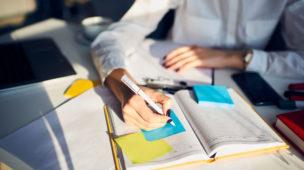 pessoa sentada em sua mesa de trabalho escrevendo em seu caderno