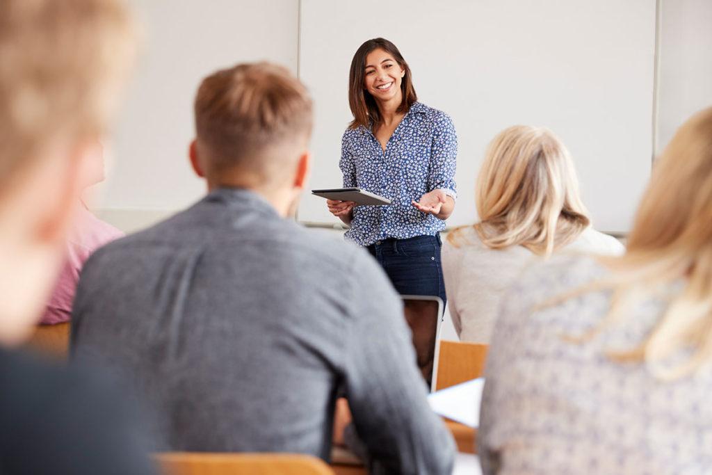 sala de aula com várias pessoas e uma professora ao centro