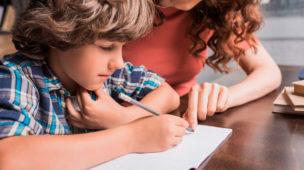 criança escrevendo em um caderno e uma mulher o auxiliando