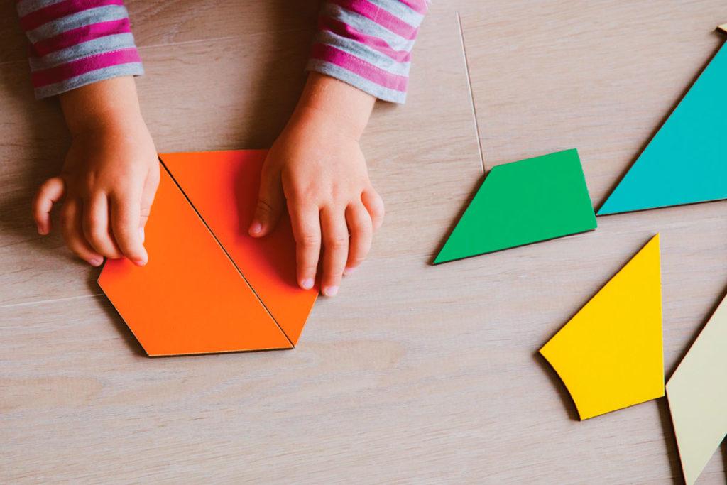 mãos de uma criança mexendo com peças coloridas