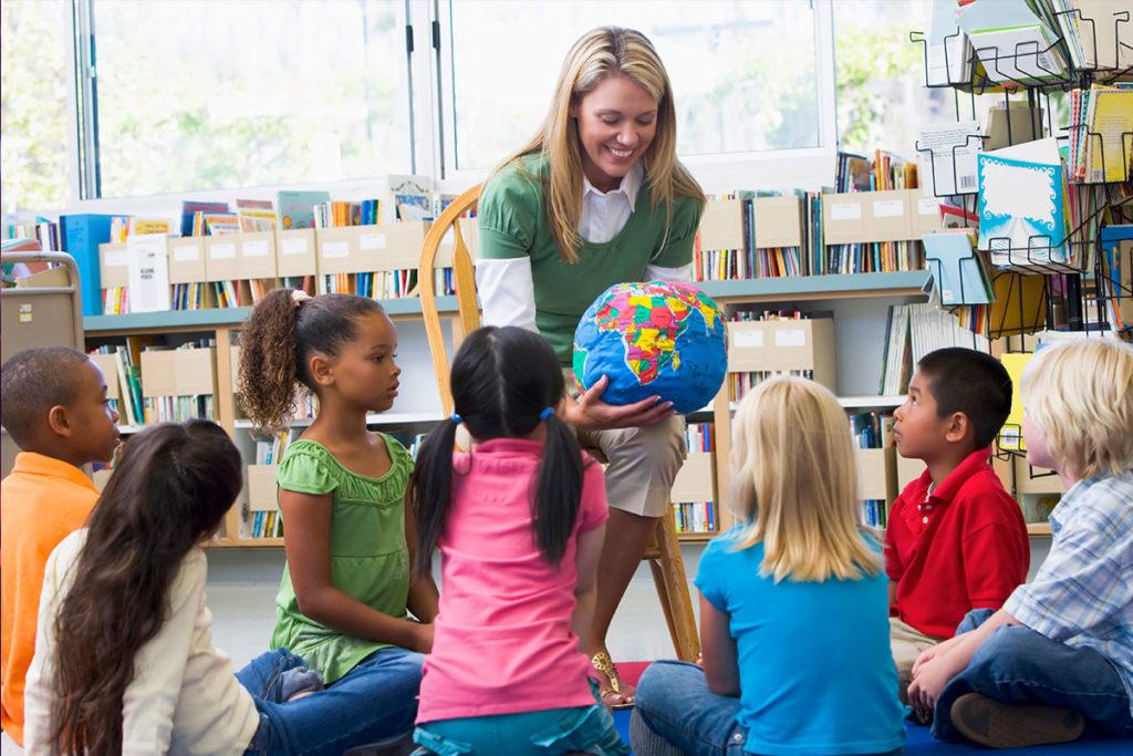 professora da educação infantil mostrando o globo terrestre aos alunos