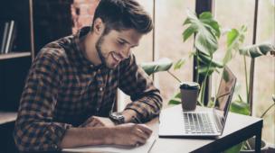 homem sorridente sentado em sua mesa de trabalho