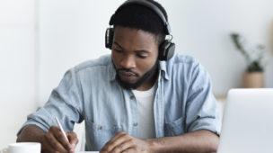 Homem com fone de ouvido na sua mesa de estudos