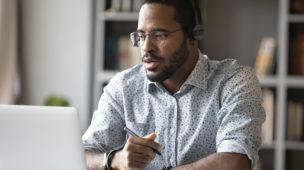 homem com fones de ouvido sentado em sua mesa de estudos