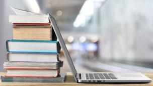 livros e notebook sobre uma mesa