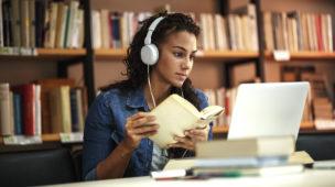 mulher com fones de ouvido na sua mesa de estudos