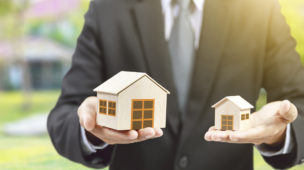 homem de terno segurando duas casas em miniatura
