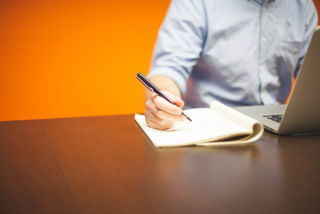 pessoa sentada utilizando seu notebook e caderno