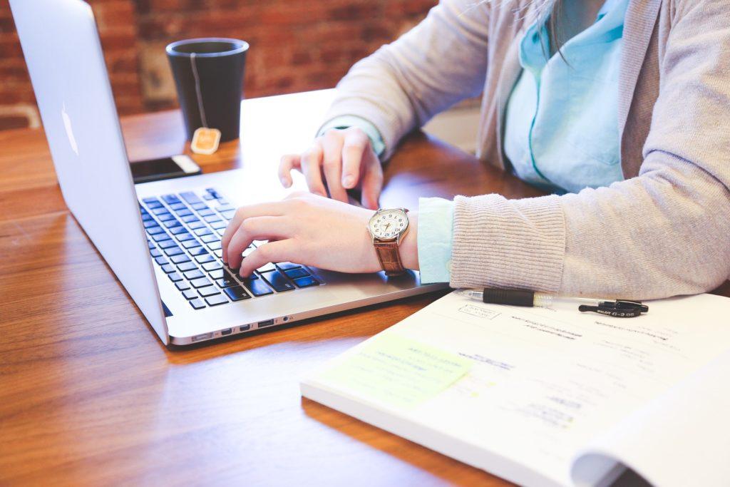 pessoa sentada trabalhando com seu notebook