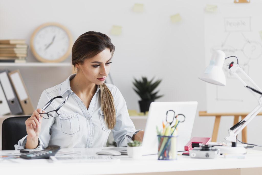 mulher bem vestida sentada na sua mesa de trabalho