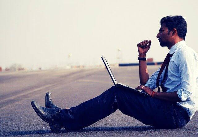 homem bem vestido sentado na rua com seu notebook em mãos