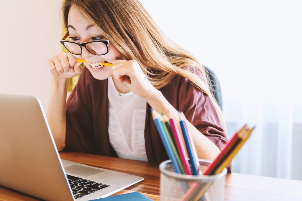 mulher mordendo um lápis e olhando para seu notebook