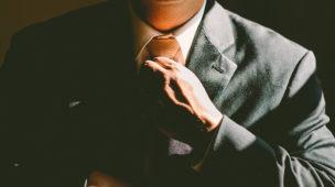 homem trajando terno com a mão na gravata