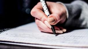 mão de uma pessoa escrevendo em um caderno