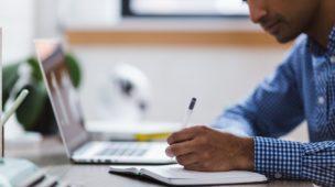 homem em seu local de trabalho escrevendo em um caderno