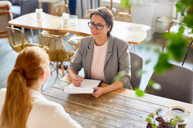 entrevistadora e entrevistada conversando no momento da entrevista de emprego