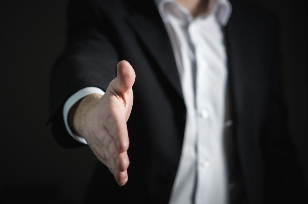 homem com o braço direito estendido simbolizando o cumprimento de mãos