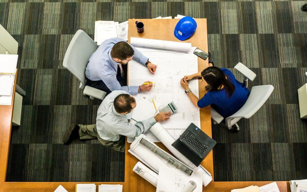 três pessoas trabalhando em um projeto e aparentam ser engenheiros