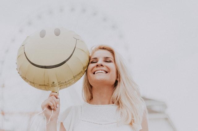 mulher sorridente segurando um balão de emoji feliz