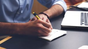 mão de uma pessoa escrevendo em um papel