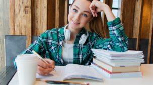 mulher sorridente estudando em sua mesa de estudos