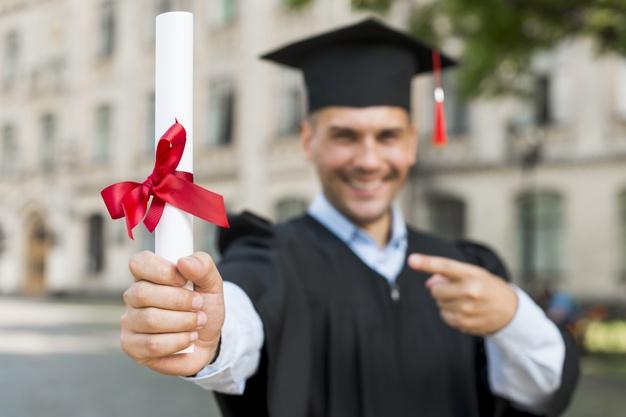 homem sorridente trajando vestes de formatura com um diploma na mão